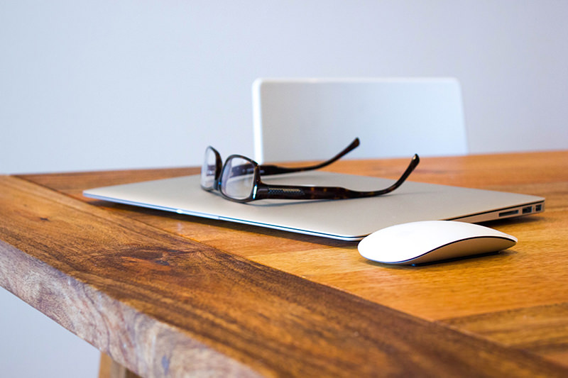 Glasses, Macbook, and mouse on a wooden table